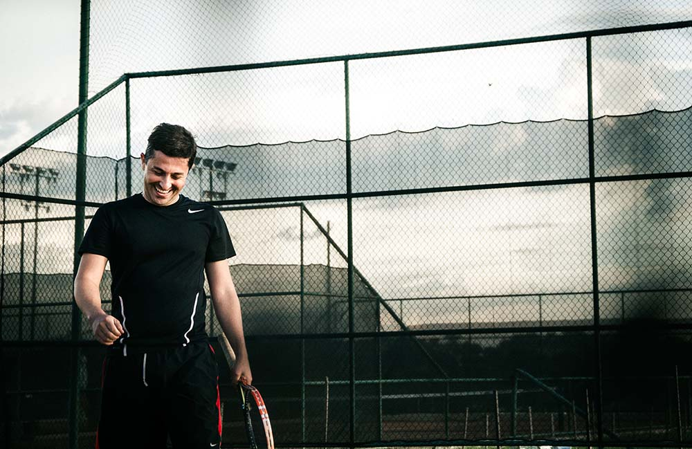 Man holding tennis racquet in front of tennis court with fencing